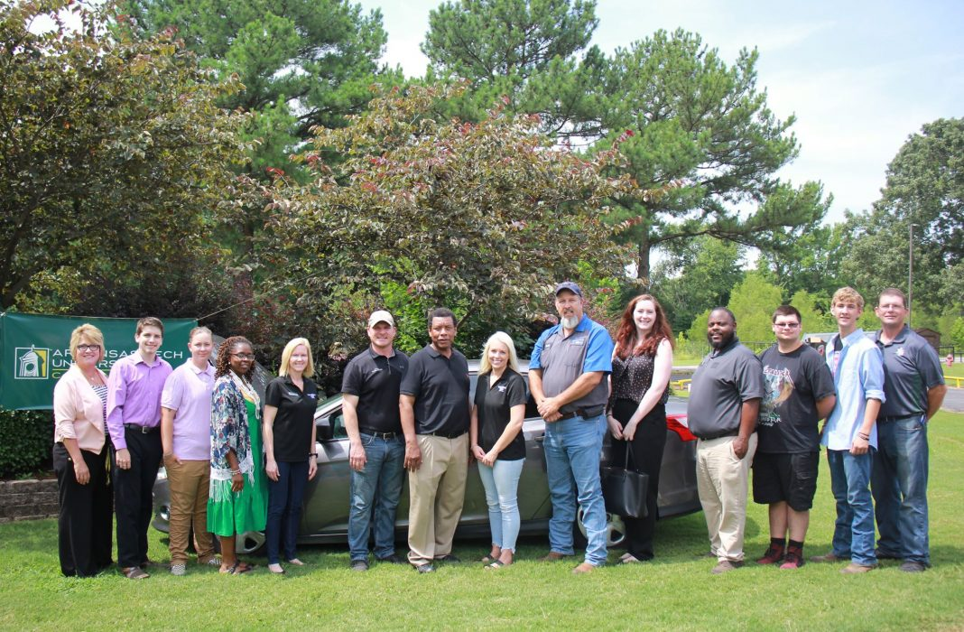 Career Center staff and students stand in front of a donated vehicle