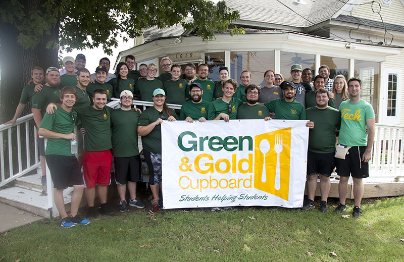 Students and faculty proudly display the Green & Gold Cupboard banner