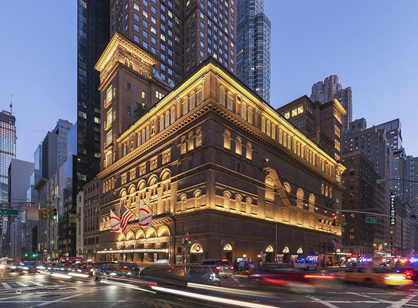 The exterior of Carnegie Hall seen at a busy time of night