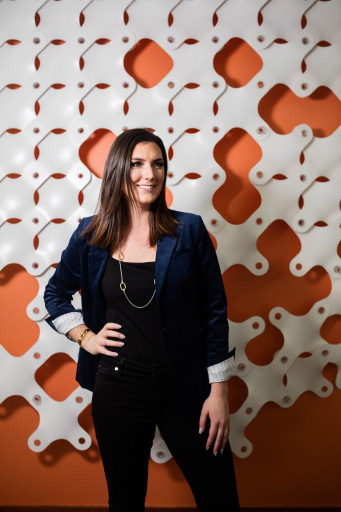 An orange patterned backdrop compliments the crushed blue velvet of Isabel's jacket