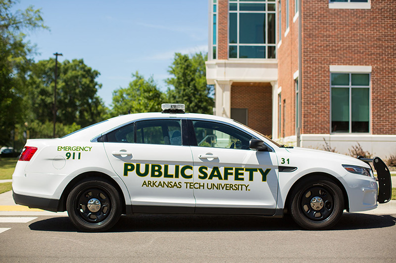 A Public Safety vehicle is seen parked by a residence hall