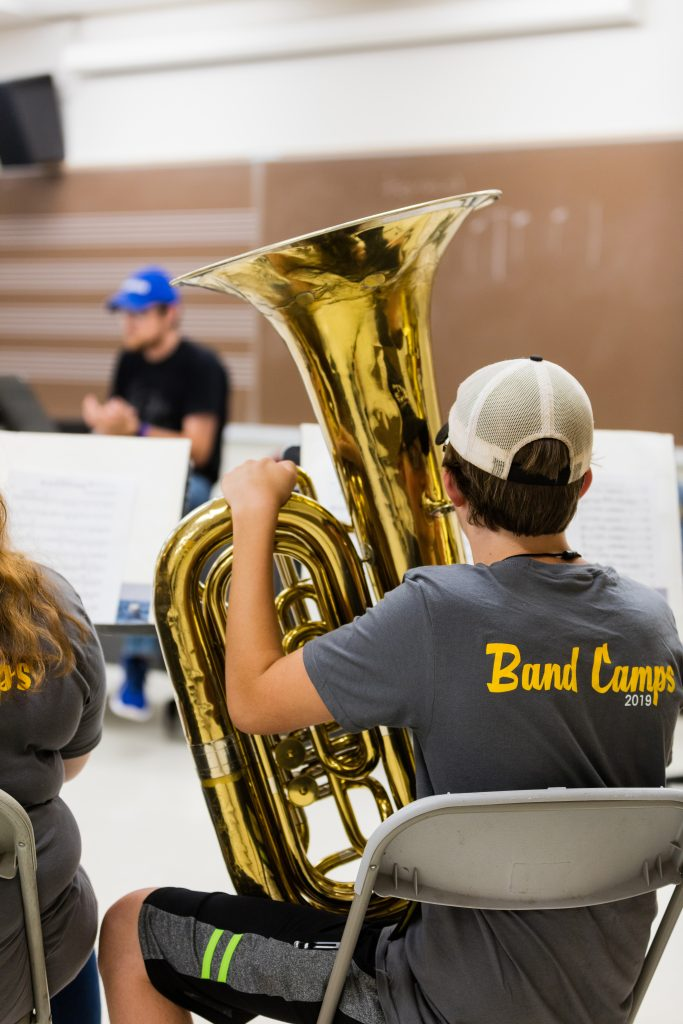 A student wearing a Band Camps 2019 tshirt holds his instrument and listens to final instructions