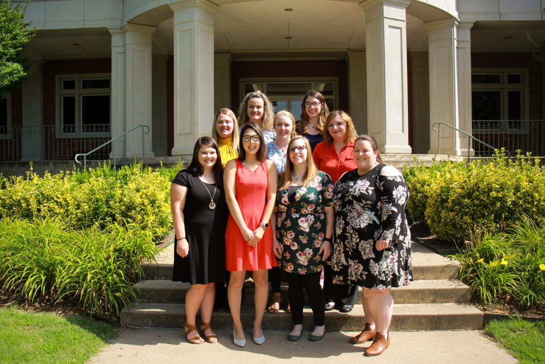 Students in the Medical Assisting program are seen standing on the steps of the library