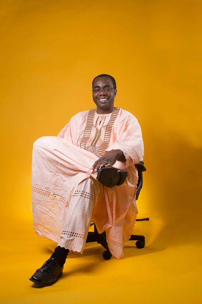 Dr. Efosa Idemudia wears traditional Nigerian garb and is seated in front of a warm yellow backdrop