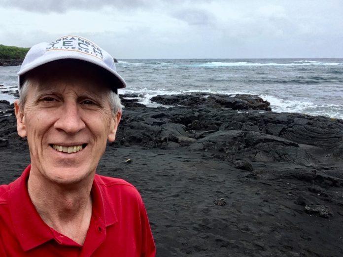 ATU alumn Bob Miller wears an ATU ball cap and stands on a black sands beach in Hawaii