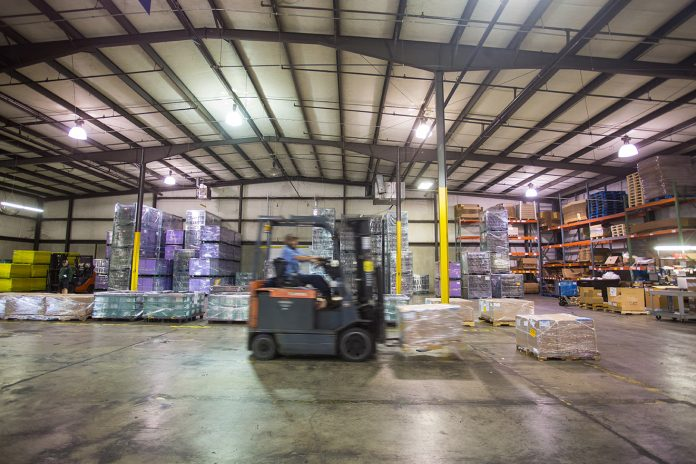 A forklift moves crates across a warehouse floor