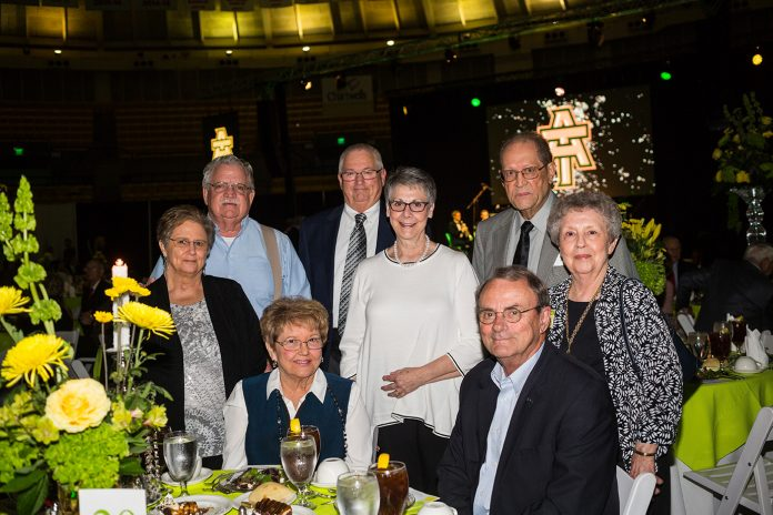 A group of alumni gather around a table