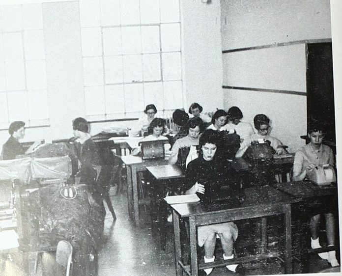 A vintage photo shows students working on typewriters and adding machines