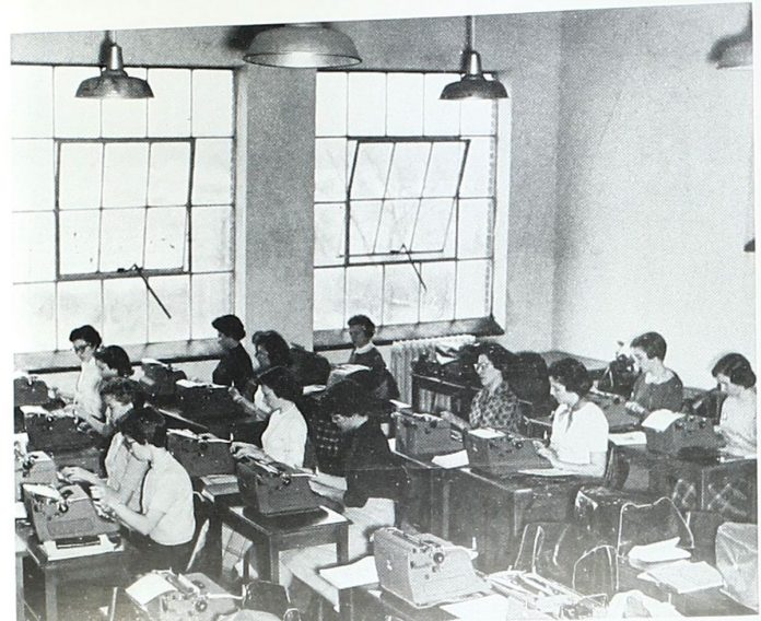 A vintage photo shows female students working on type writers in a lofty room with open windows