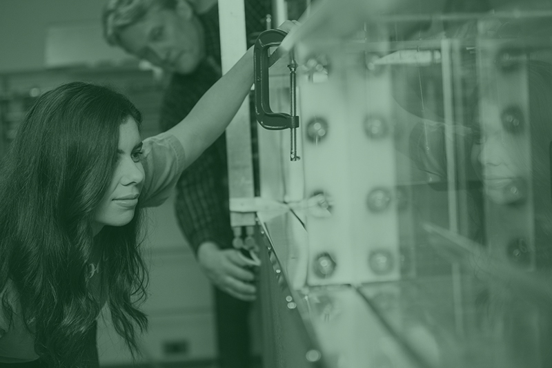 An engineering student looks closely at a piece of equipment