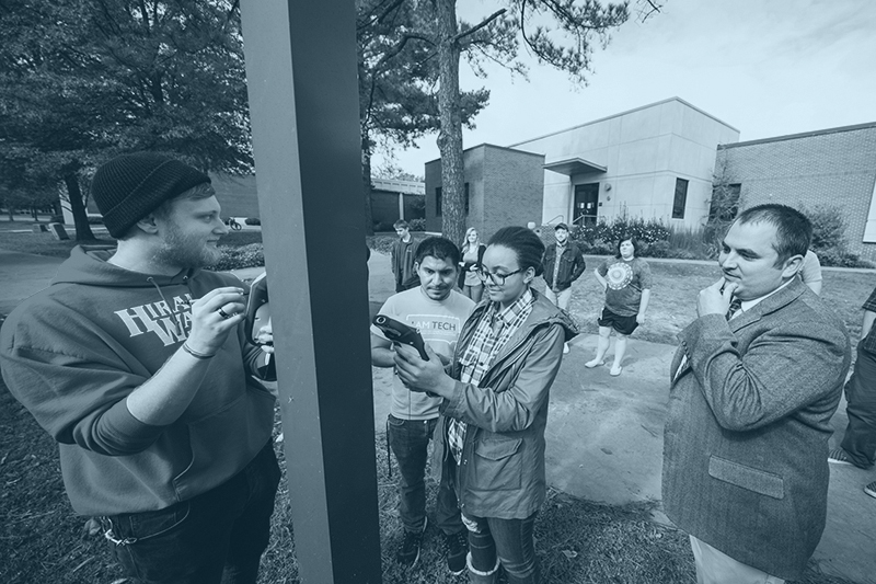 A group of students walks across campus collecting GPS data