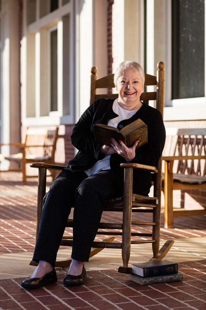 Faculty member Jan Jenkins sits in a rocking chair on the porch of the Ross Pendergraft Library and Technology Center