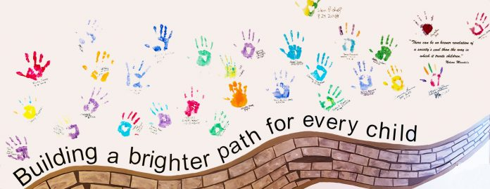 A mural on the wall at RVCAC displays the hand prints and signatures of those involved with building a brighter path for every child