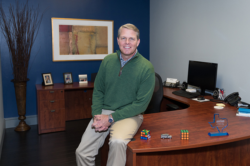 Brent Garrett sits on the corner of a large wooden desk with his hands folded in his lap