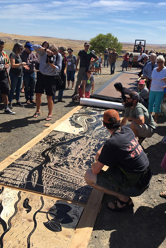 Fellow artists are seen printing the full 66-foot piece