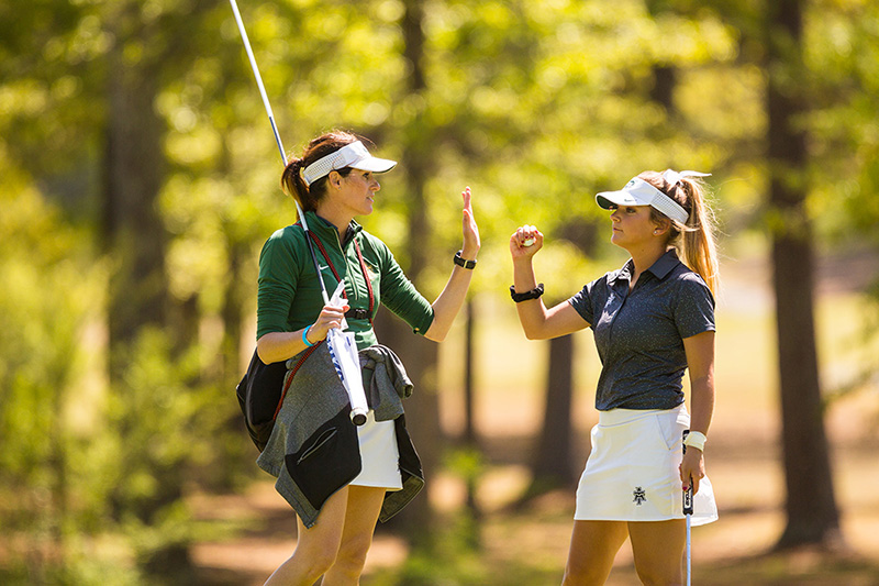 Coach Amy Anderson offers encouragement to a team member after they sink a putt