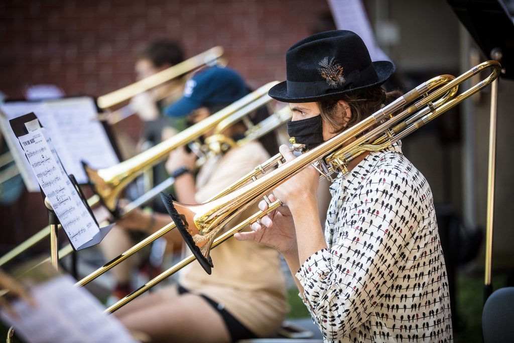 A trombonist practices outdoors.