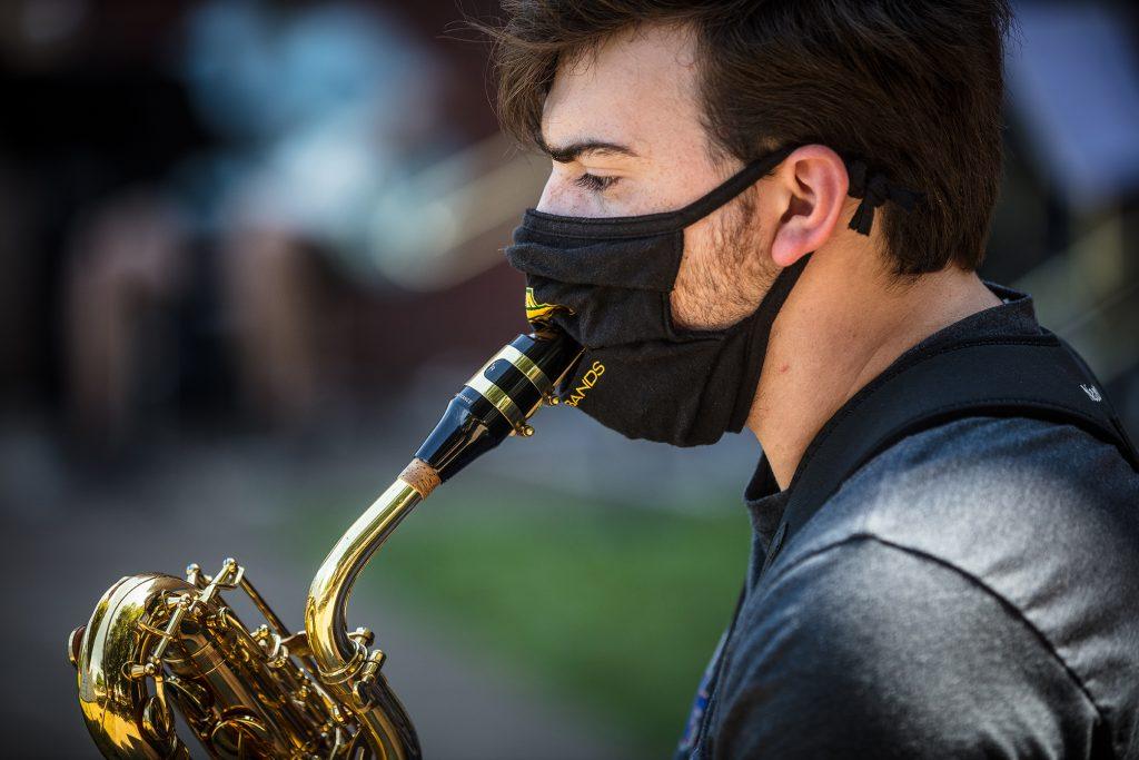 A baritone saxophone player, up close and masked.