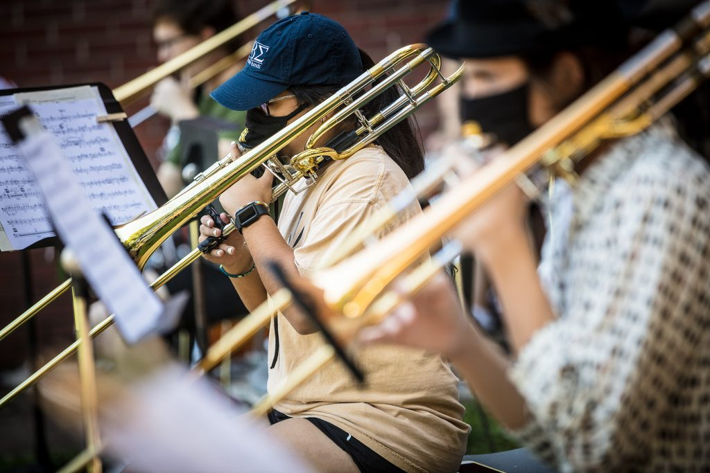 A female trombonist, masked, up-close, playing outdoors.
