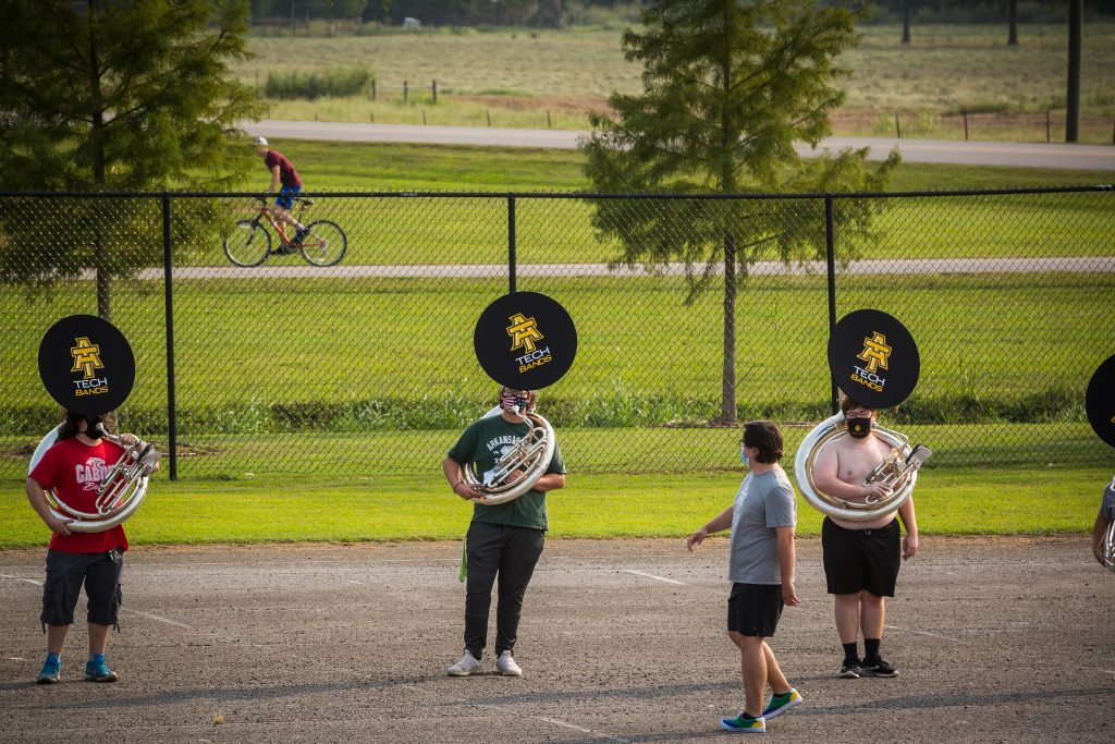 Michael Barker giving directions to the sousaphone line during outdoor practice.